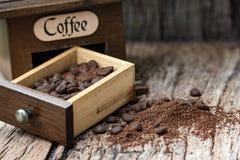 Кофейные зерна и точильщик с деревянной предпосылкой стоковая фотография