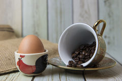 Кофейные зерна и яичко на таблице (стиль натюрморта) Стоковое Фото