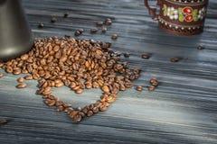 Кофейные зерна и Cezve в форме сердца на деревянной предпосылке Стоковая Фотография