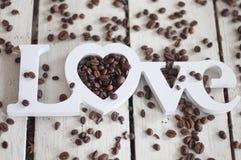 Кофейные зерна, кофе, кофе влюбленности, печенья, белая предпосылка, деревянная предпосылка Стоковая Фотография