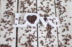 Кофейные зерна, кофе, кофе влюбленности, печенья, белая предпосылка, деревянная предпосылка Стоковое фото RF