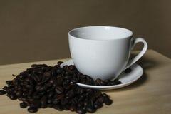 Кофейные зерна, кружки белого кофе помещенные на деревянном Стоковое Изображение
