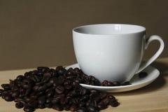 Кофейные зерна, кружки белого кофе помещенные на деревянном Стоковое фото RF