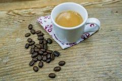 Кофейные зерна наряду с чашкой кофе молока Стоковая Фотография