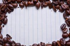 Кофейные зерна на бумаге для примечаний Стоковая Фотография RF
