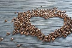 Кофейные зерна на деревянной предпосылке сердце формы кофе фасолей Валентайн дня s Стоковая Фотография