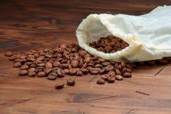 Кофейные зерна на деревянной разбросанной предпосылке стоковое фото rf