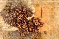 Кофейные зерна на деревянной таблице на старой стене текстурировали предпосылку Стоковое фото RF