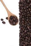 Кофейные зерна на деревянных ложке и кофейных зернах на белой предпосылке Стоковые Изображения
