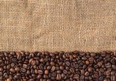 Кофейные зерна на естественной предпосылке джута, взгляд сверху Стоковые Фото