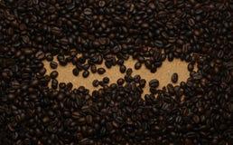 Кофейные зерна на коричневой бумаге, можно использовать как задняя часть Стоковое Изображение RF