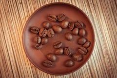 Кофейные зерна на коричневом керамическом поддоннике Стоковые Фото