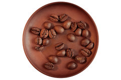 Кофейные зерна на коричневом керамическом поддоннике Стоковое Фото