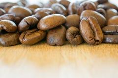 Кофейные зерна на крупном плане деревянного стола Стоковое фото RF