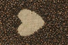 Кофейные зерна на предпосылке джута Стоковая Фотография RF
