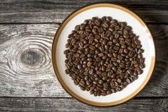 Кофейные зерна на плите на взгляд сверху деревянного стола стоковое изображение