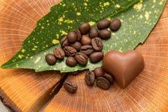 Кофейные зерна на списке с сердцем шоколада на пне Стоковые Фото
