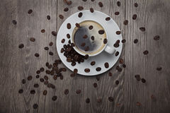 кофейные зерна объезжая над кофейной чашкой Стоковое фото RF