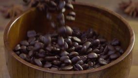 Кофейные зерна падают на таблицу в деревянном блюде Серая предпосылка Падение и полет семян видео- видеоматериал