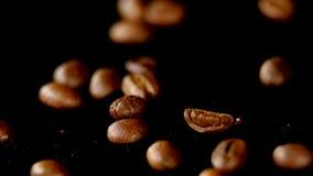 Кофейные зерна - падающ макрос 96 fps снял кофейных зерен падая на черную поверхность Красивая родовая съемка для любых акции видеоматериалы