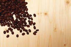 Кофейные зерна разбросанные на таблицу стоковое изображение