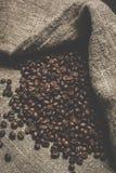 Кофейные зерна разливая вне Стоковые Фото