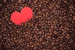 Кофейные зерна с красным бумажным сердцем Стоковые Фото