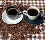 2 кофейные чашки и кофейного зерна на checkered ткани Стоковое Изображение