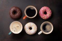 Кофейные чашки и красочные donuts Стоковые Изображения