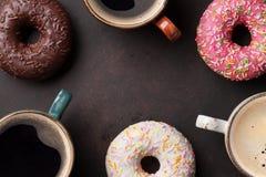 Кофейные чашки и красочные donuts Стоковое Изображение RF