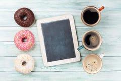 Кофейные чашки и красочные donuts Стоковые Фото