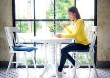 Кофе азиатской женщины выпивая на белой таблице Стоковые Изображения RF