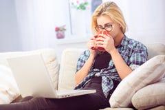 Кофе дамы выпивая перед компьтер-книжкой Стоковое фото RF