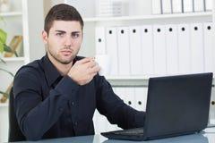 Кофе бизнесмена выпивая в его офисе Стоковые Фотографии RF