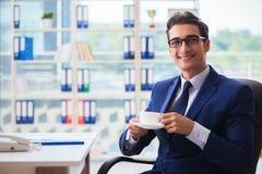 Кофе бизнесмена выпивая в офисе во время пролома Стоковая Фотография RF