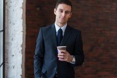 Кофе бизнесмена выпивая в офисе стоя близко окно смотря камеру Стоковое фото RF