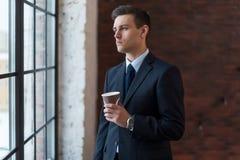 Кофе бизнесмена выпивая в офисе стоя близко окно Стоковое Фото