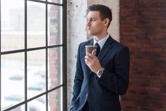 Кофе бизнесмена выпивая в офисе стоя близко окно Стоковые Изображения