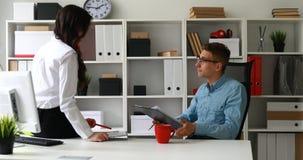 Кофе бизнесмена выпивая и дело обсуждать при секретарша сидя на таблице акции видеоматериалы
