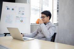Кофе бизнесмена выпивая и работа в офисе Стоковые Фото