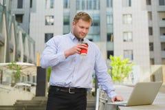 Кофе бизнесмена выпивая и работа на компьтер-книжке внешней Стоковое Изображение