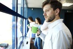 Кофе бизнесмена выпивая и смотреть и усмехаться на камере, в современном офисе Стоковые Фотографии RF