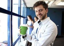 Кофе бизнесмена выпивая и смотреть и усмехаться на камере, в современном офисе Стоковые Изображения