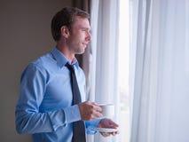 Кофе бизнесмена выпивая и смотреть снаружи Стоковое Изображение