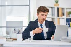 Кофе бизнесмена выпивая на столе в офисе Стоковые Изображения