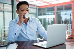 Кофе бизнесмена выпивая пока работающ на компьтер-книжке Стоковая Фотография