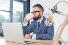 Кофе бизнесмена выпивая пока работающ на рабочем месте с компьтер-книжкой в офисе Стоковое Изображение RF