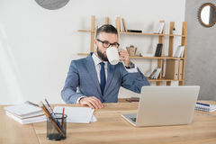 Кофе бизнесмена выпивая пока работающ на рабочем месте с компьтер-книжкой в офисе Стоковые Фото