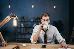 Кофе бизнесмена выпивая пока работающ на современном офисе Стоковое Изображение