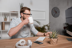 Кофе бизнесмена выпивая пока смотрящ монитор компьютера и сидящ на рабочем месте Стоковая Фотография